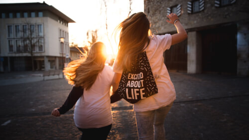 2 women running, one has rucksack that says excited about life
