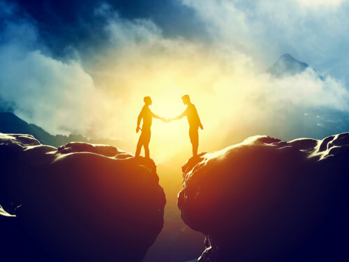 Two people handshake over mountains precipice. Business, deal, connection concepts